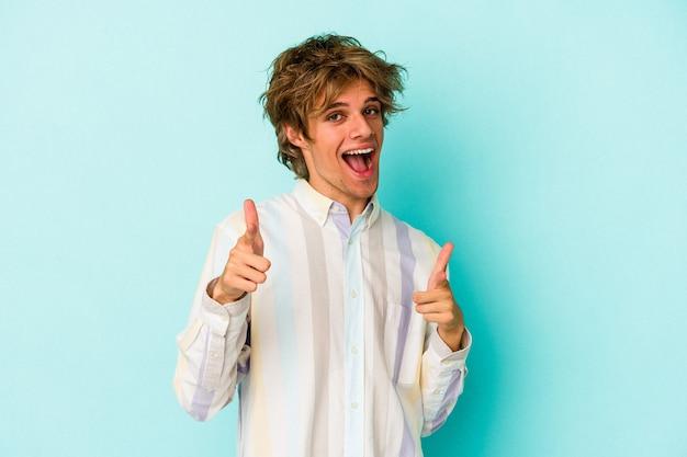 Jeune homme de race blanche avec maquillage isolé sur fond bleu sourires joyeux pointant vers l'avant.