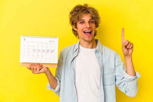Jeune homme de race blanche avec maquillage tenant un calendrier isolé sur fond jaune montrant le numéro un avec le doigt.