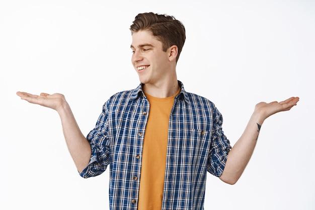 Jeune homme de race blanche montrant les mains ouvertes, tenant l'article et regardant la paume avec une place vide pour vos produits, souriant heureux, faisant du shopping, debout sur du blanc