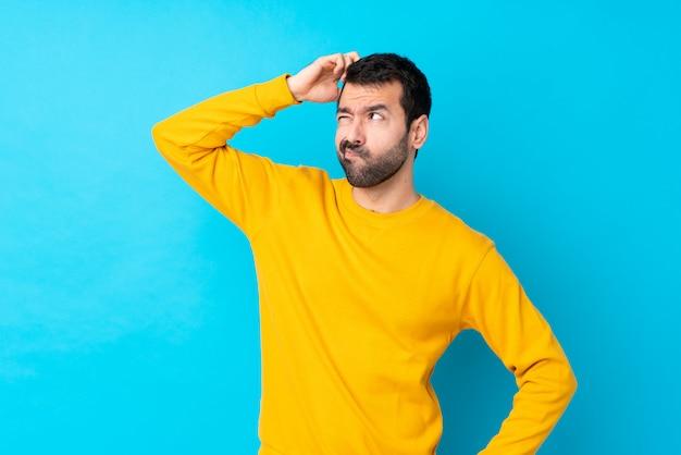 Jeune homme de race blanche sur mur bleu isolé ayant des doutes tout en se grattant la tête