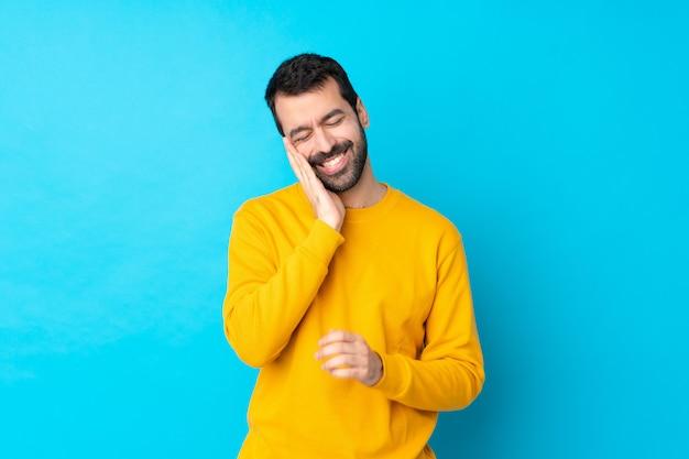 Jeune homme de race blanche sur mur bleu isolé avec maux de dents