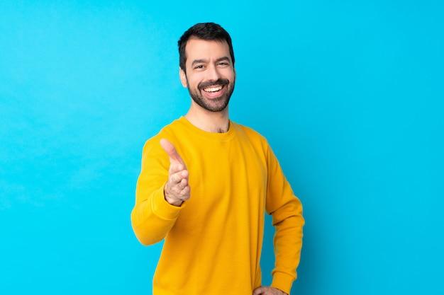 Jeune homme de race blanche sur mur bleu isolé se serrant la main pour fermer une bonne affaire