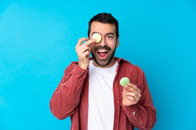 Jeune homme de race blanche sur un mur bleu isolé tenant des macarons français colorés
