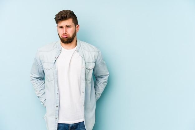 Jeune homme de race blanche sur le mur bleu souffle les joues, a une expression fatiguée