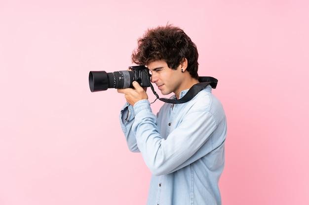 Jeune homme de race blanche sur un mur rose isolé avec un appareil photo professionnel