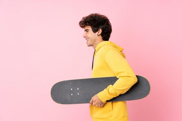 Jeune homme de race blanche sur mur rose isolé avec patin en position latérale