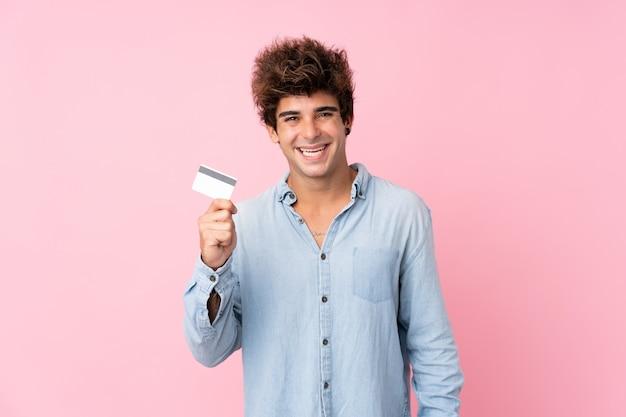 Jeune homme de race blanche sur mur rose isolé tenant une carte de crédit