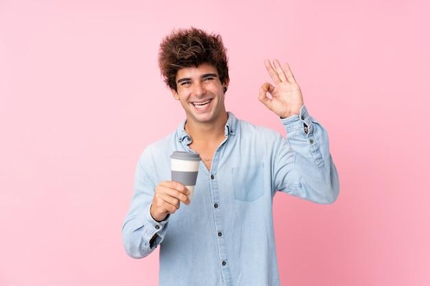 Jeune homme de race blanche sur un mur rose isolé tenant du café à emporter tout en faisant signe ok
