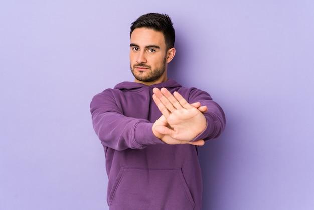 Jeune homme de race blanche sur mur violet debout avec la main tendue montrant le panneau d'arrêt