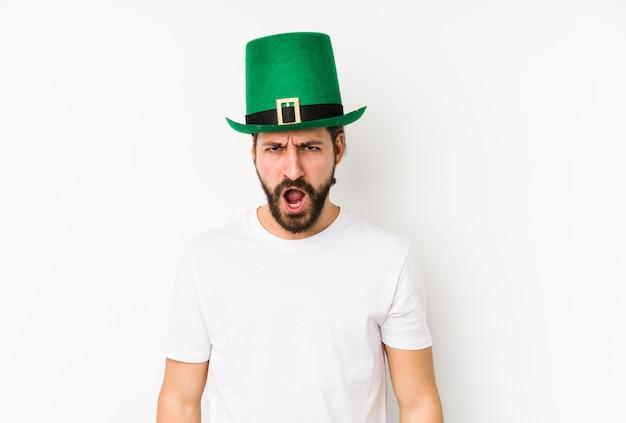 Jeune homme de race blanche portant un chapeau de saint patrick criant très en colère et agressif.