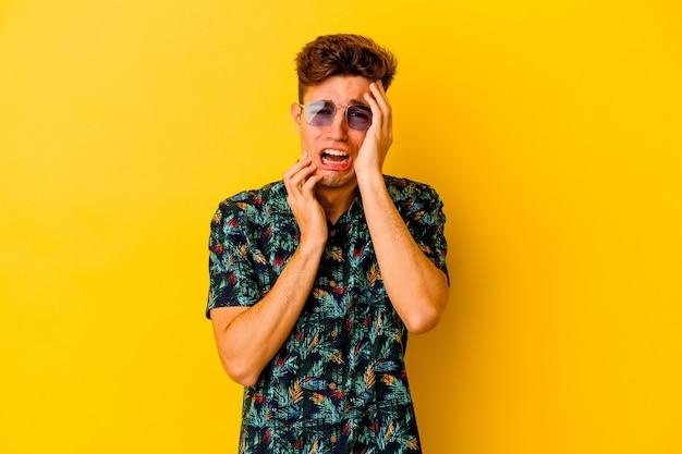 Jeune homme de race blanche portant une chemise hawaïenne isolé sur mur jaune pleurnicher et pleurer de façon inconsolable