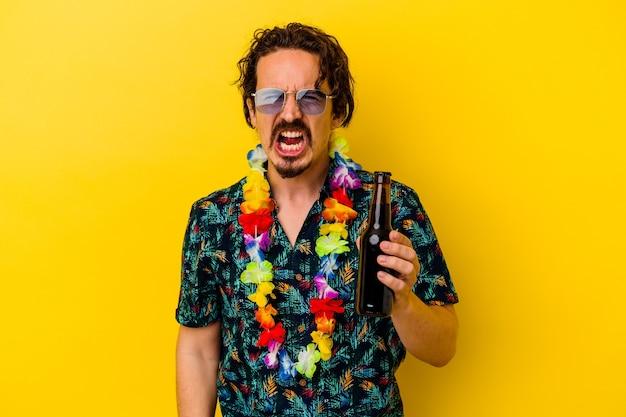 Jeune homme de race blanche portant un collier hawaïen tenant une bière criant très en colère et agressif.