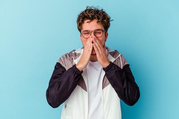 Jeune homme de race blanche portant des lunettes isolé sur fond bleu disant un potin, pointant vers le côté rapportant quelque chose.