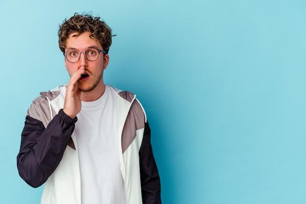 Un jeune homme de race blanche portant des lunettes isolé sur fond bleu dit une nouvelle secrète de freinage à chaud et regarde de côté