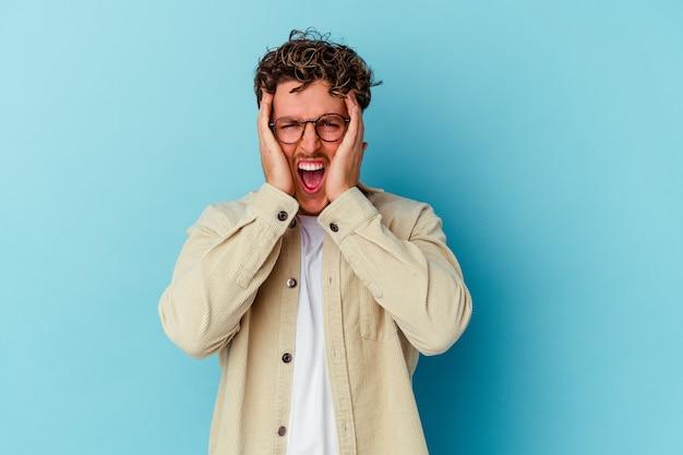 Jeune homme de race blanche portant des lunettes isolées sur fond bleu couvrant les oreilles avec les mains essayant de ne pas entendre un son trop fort.