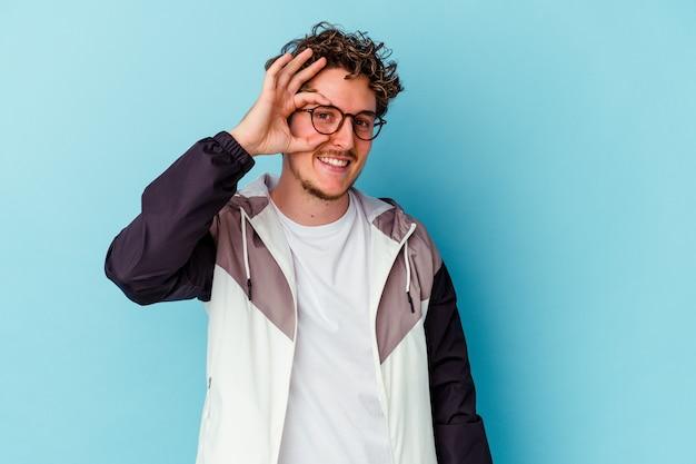 Jeune homme de race blanche portant des lunettes isolées sur fond bleu excité en gardant un geste correct sur les yeux.