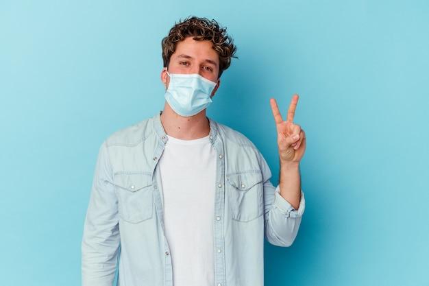 Jeune homme de race blanche portant un masque antiviral isolé sur mur bleu joyeux et insouciant montrant un symbole de paix avec les doigts