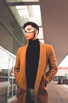 Jeune homme de race blanche portant un masque marron avec un manteau marron dans la rue