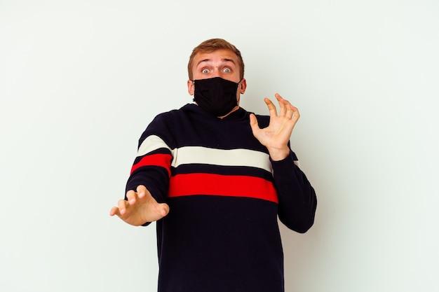 Jeune homme de race blanche portant un masque pour virus isolé sur un mur blanc étant choqué en raison d'un danger imminent