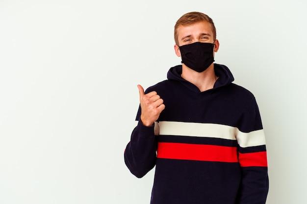 Jeune homme de race blanche portant un masque pour virus isolé sur un mur blanc souriant et levant le pouce vers le haut