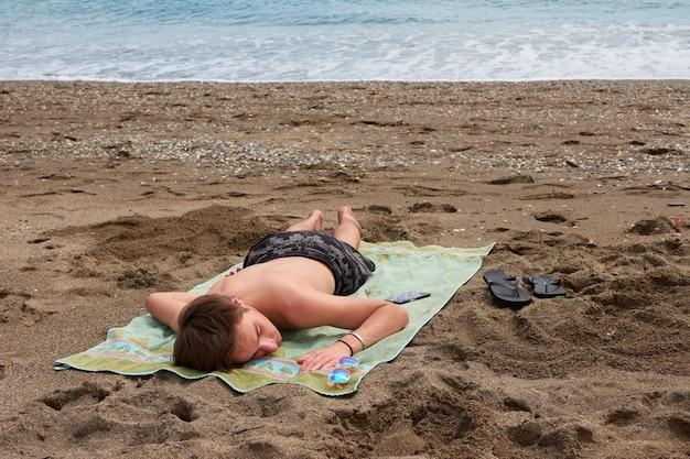 Un jeune homme de race blanche portant sur une serviette sur une plage