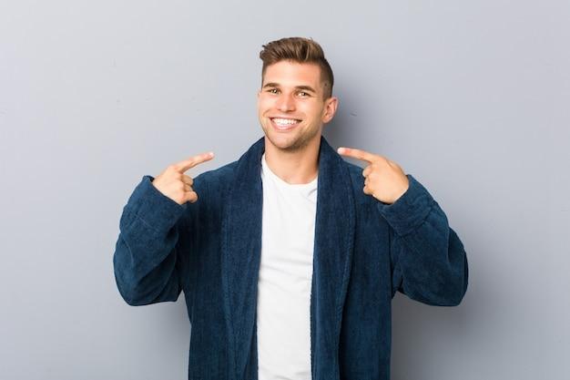 Jeune homme de race blanche portant des sourires de pyjama, pointer du doigt la bouche.