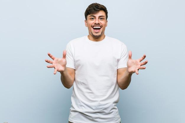 Jeune homme de race blanche portant un tshirt blanc célébrant une victoire ou un succès