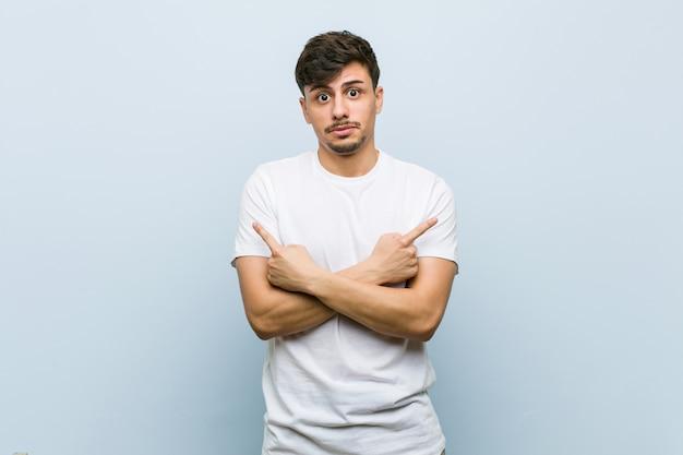 Jeune homme de race blanche portant un tshirt blanc pointe de côté, tente de choisir entre deux options.