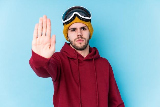 Jeune homme de race blanche portant un vêtement de ski debout avec la main tendue montrant le panneau d'arrêt