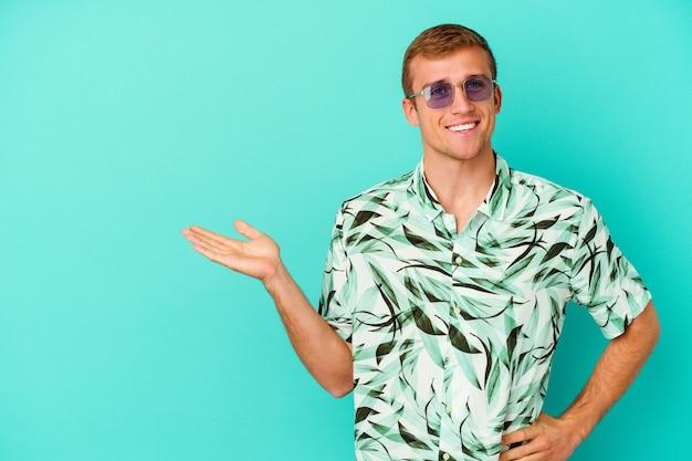 Jeune homme de race blanche portant des vêtements d'été isolés sur fond bleu montrant un espace de copie sur une paume et tenant une autre main sur la taille.