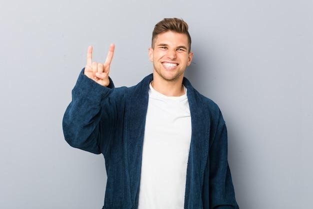 Jeune homme de race blanche en pyjama montrant un geste de cornes comme un concept de révolution.