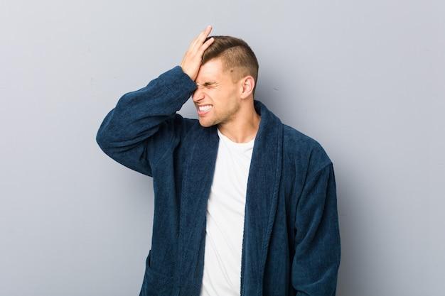 Jeune homme de race blanche en pyjama oubliant quelque chose, claquant le front avec palme et fermant les yeux.