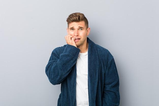 Jeune homme de race blanche en pyjama se ronger les ongles, nerveux et très inquiet.