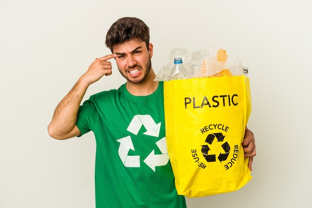 Jeune homme de race blanche recyclage du plastique isolé sur fond blanc montrant un geste de déception avec l'index.