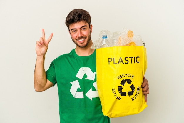 Jeune homme de race blanche recyclage du plastique isolé sur fond blanc montrant le numéro deux avec les doigts.