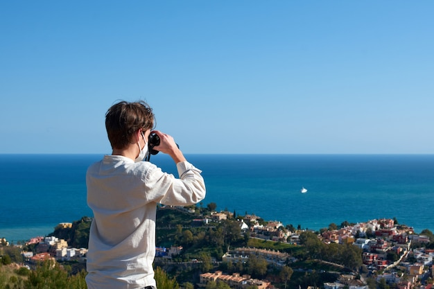 Un jeune homme de race blanche regardant une vue sur la mer avec des jumelles