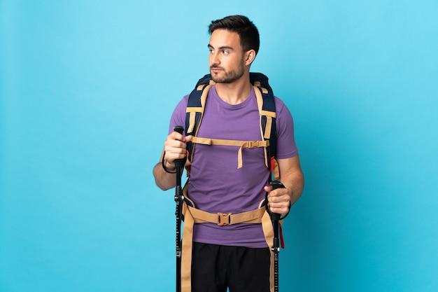 Jeune homme de race blanche avec sac à dos et bâtons de randonnée isolés sur bleu à la recherche sur le côté