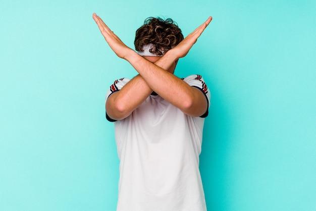 Jeune homme de race blanche sport isolé sur fond bleu en gardant les deux bras croisés, concept de déni.