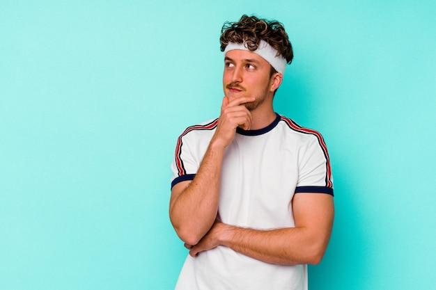 Jeune homme de race blanche sport isolé sur fond bleu à la recherche de côté avec une expression douteuse et sceptique.