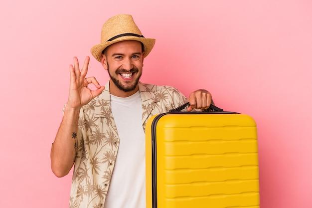 Jeune homme de race blanche avec des tatouages allant voyager isolé sur fond rose joyeux et confiant montrant un geste correct.