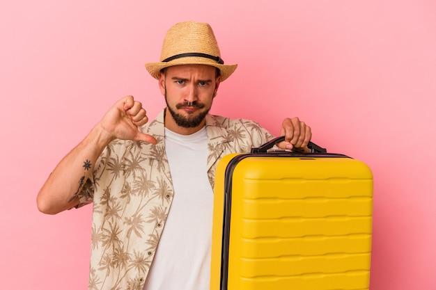 Jeune homme de race blanche avec des tatouages allant voyager isolé sur fond rose montrant un geste d'aversion, les pouces vers le bas. notion de désaccord.