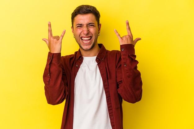 Jeune homme de race blanche avec des tatouages isolés sur fond jaune montrant un geste de cornes comme concept de révolution.