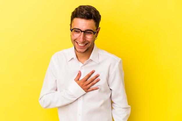 Jeune homme de race blanche avec des tatouages isolés sur fond jaune en riant en gardant les mains sur le cœur, concept de bonheur.
