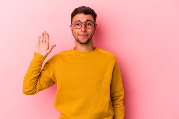 Jeune homme de race blanche avec des tatouages isolés sur fond jaune souriant joyeux montrant le numéro cinq avec les doigts.