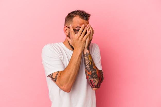 Jeune homme de race blanche avec des tatouages isolés sur fond rose clignote à travers les doigts effrayés et nerveux.