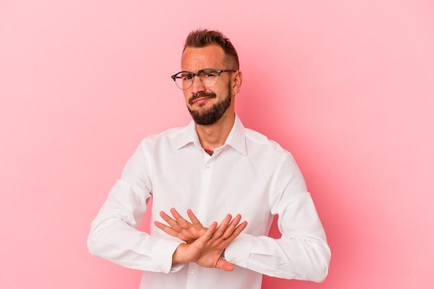Jeune homme de race blanche avec des tatouages isolés sur fond rose faisant un geste de déni