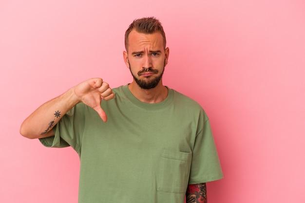Jeune homme de race blanche avec des tatouages isolés sur fond rose montrant un geste d'aversion, les pouces vers le bas. notion de désaccord.