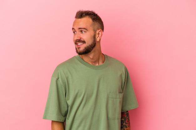 Jeune homme de race blanche avec des tatouages isolés sur fond rose regarde de côté souriant, joyeux et agréable.