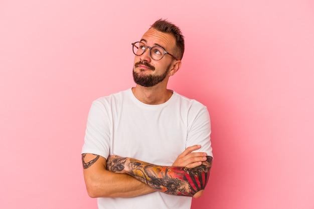 Jeune homme de race blanche avec des tatouages isolés sur fond rose rêvant d'atteindre des objectifs et des buts