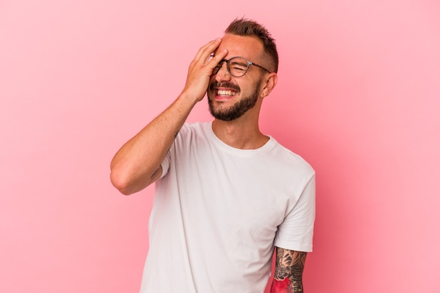 Jeune homme de race blanche avec des tatouages isolés sur fond rose riant heureux, insouciant, émotion naturelle.